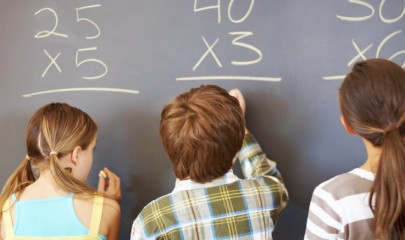 Children writing equation solution on chalkboard